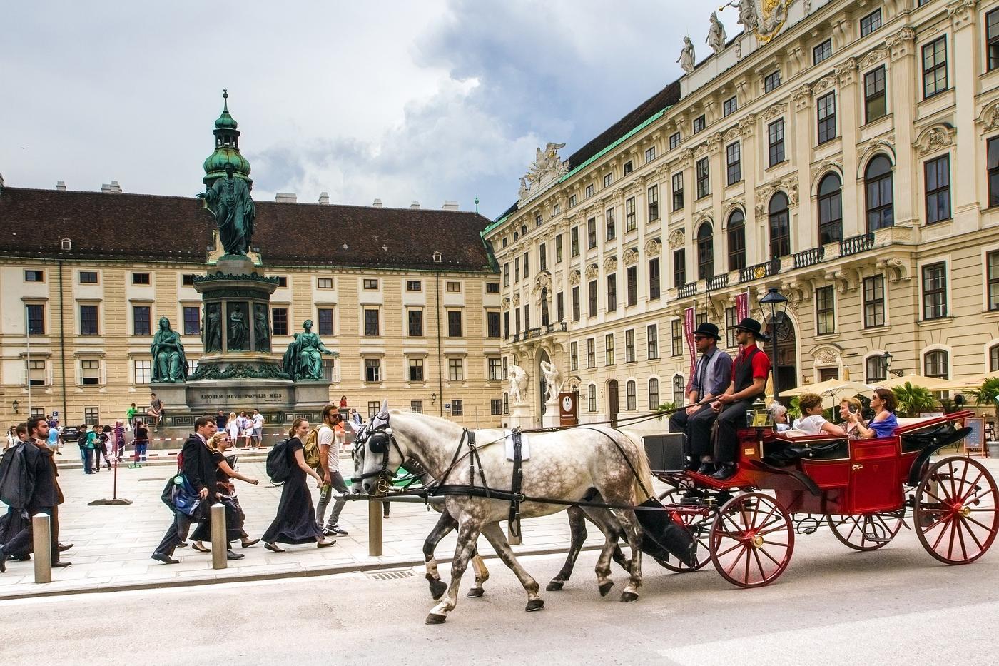Fiaker fährt vor Hofburg im 1. Bezirk von Wien