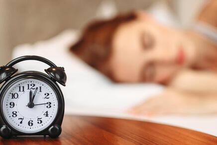 Wecker und schlafende Frau