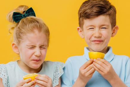 Ein Mädchen und ein Junge kosten eine Zitrone und verziehen ihr Gesicht.
