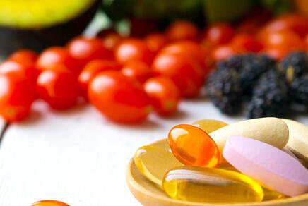Vitamintabletten auf einem Holzlöffel mit Obst und Gemüse im Hintergrund