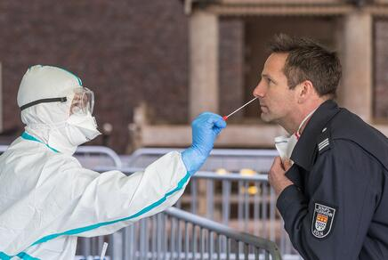 Eine Person in Schutzkleidung entnimmt einen Nasen-Rachen-Abstrich eines Mannes