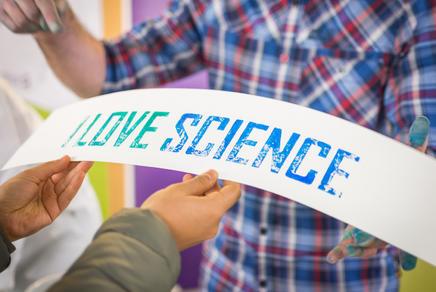 """Auf dem Bild ist eine Person in einem karierten Hemd zu sehen, die auf einen Schriftzug """"I love science"""" zeigt."""