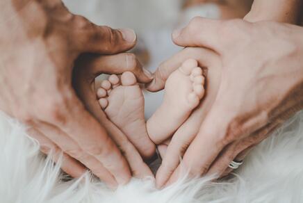 Füße eines Neugeborenen und Hände von Erwachsenen