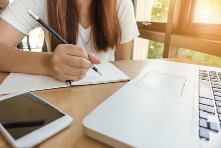 Mädchen das zu Hause vor einem Laptop sitzt und schreibt